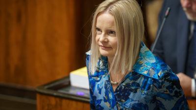 Perussuomalaisten kansanedustaja Riikka Purra omalla paikallaan eduskunnan istuntosalissa.