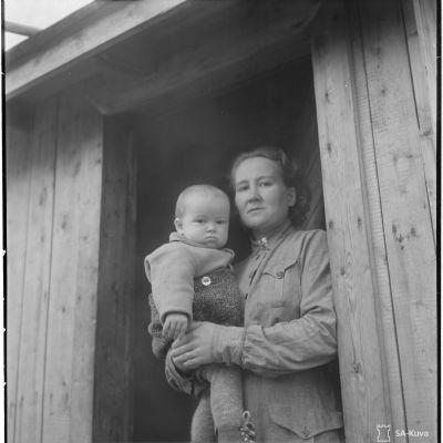 Rajamiehen perhe. Ylikersantti Elna Kuoskun vaimo Savukoskelta. Vaimo toimii kenttälottana pitäen lapsen mukanaan silloin kun mies on rintamalla.