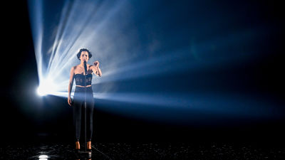 Sångerskan Barbara Pravi med stark strålkastare bakom sig