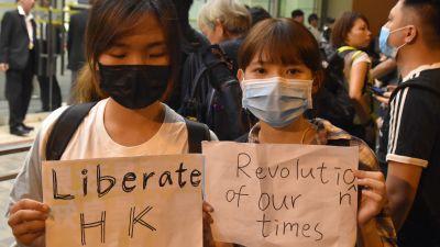 Två kvinnor håller upp skyltar där det står befria Hongkong, vår tids revolution.