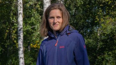 Elina Leppänen tittar in i kameran och ler.
