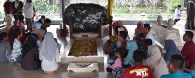 Människor sitter vid Sukarnos grav.