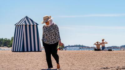 Nainen kävelee hiekkarannalla sandaalit kädessään.