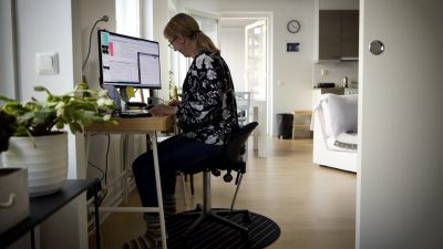 En kvinna sitter inne i sitt hem och jobbar vid en dator.