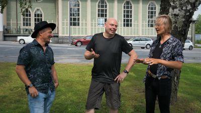 Tre män står på en gräsmatta bredvid en gata.