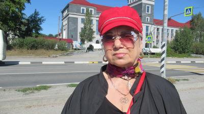 En kvinna fotograferad utomhus framför en stor byggnad. Kvinnan är färggrannt klädd, med röda solglasöhon och stora smycken.