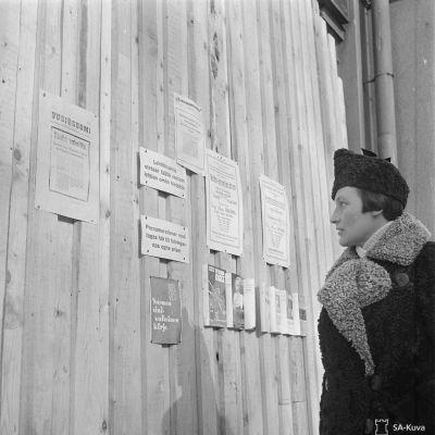 En kvinna i Helsingfors läser om freden i mars, 1940