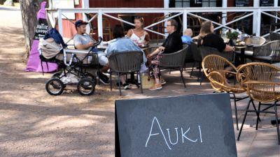 """En familj med en barnvagn sitter på en uteservering i Nagu gästhamn. I förgrunden en skylt med texten """"Auki""""."""