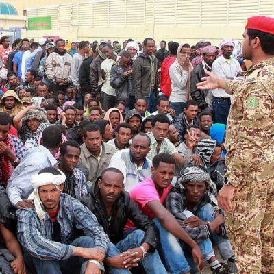 Ulkomaalaisia siirtotyöläisiä istumassa maassa poliisin edessä.