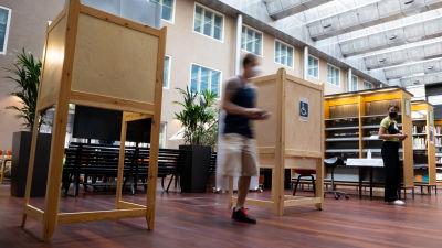 Kaksi äänestyskoppia kirjaston äänestyspisteellä. Mies kävelee ulos äänestyskopista, vaalityöntekijä katsoo sivusta. Miestä ei tunnista kuvasta.