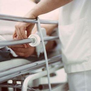 En sjukskötare invid en sjukhussäng.