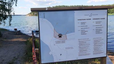 En skylt med en karta över var hundar får simma på hundstrand Tassnäs.
