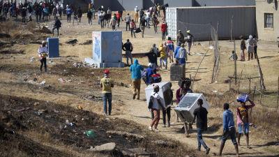 Invånare i Soweto utanför Johannesburg bär hem varor, som ugnar och kylskåp, som plundrades från en närliggande varuhus.