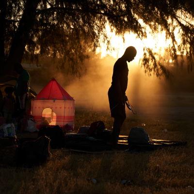 Ihminen seisoo vastavaloon ilta-aurinkoon nurmella, johon hän on laskenut isot kantamuksensa.