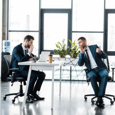 Två män i kostym sitter och skvallrar i modernt kontorsutrymme