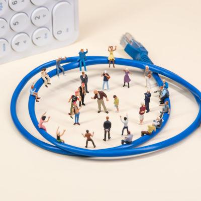 Leksaksfigurer uppställda i ring vid en internet-kabel.