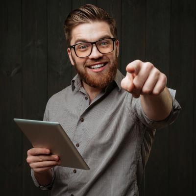 En ung man med skägg pekar mot kameran och ser glad ut. I andra handen har han en pekplatta.