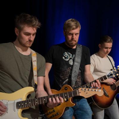 tre manliga gitarrister
