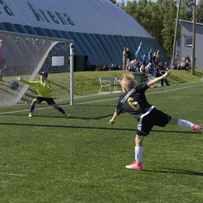 En spelare från SJK har nyss sparkat bollen i målet. I ögonblicksbilden ser man målvakten sträcka sig mot bollen.