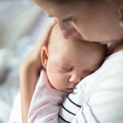 Mamma håller baby mot sitt bröst.