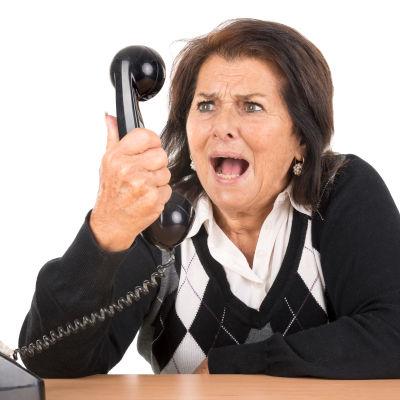 Arg kvinna skriker i telefonen.
