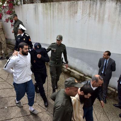 Marockansa poliser eskorterar en grupp av de misstänkta männen.