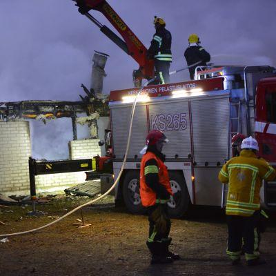 Paloauto ja palomiehiä tulipalossa tuhoutuneen tiiliverhoillun rivitalon luona.