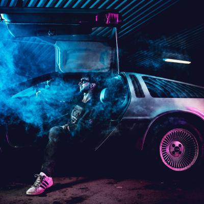Robert Parker sitter svartklädd i ett dis av rök och blått och rosa ljus i en deloreanbil med dörren öppen.