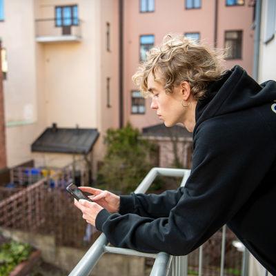 Poika parvekkeella puhelin kädessä, näytöllä Yle Areena