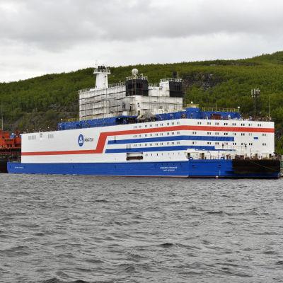 Den ryska kärnkraftsdrivna båten ligger vid hamnen. Båten är väldigt kubisk till sin design och är vit med blåa och röda streck.