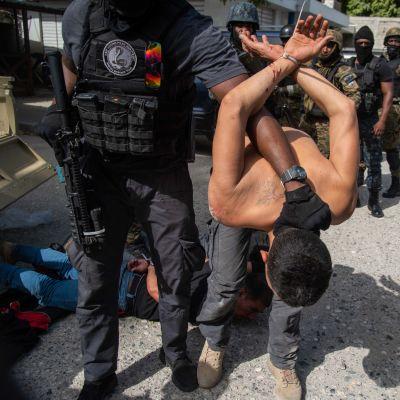 Poliisi pitää kiinni pidättämäänsä miestä. Toinen pidätetty makaa maassa.