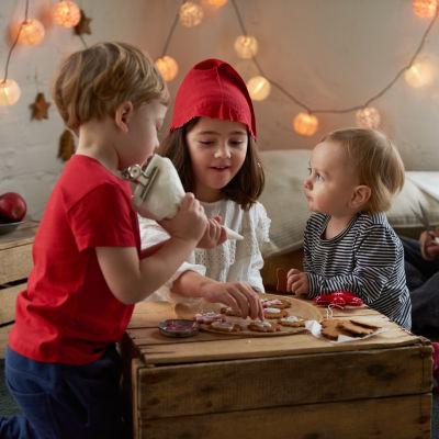 barn dekorerar pepparkakor och mamma tittar på