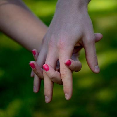 käsi kädessä, toisella punaista kynsilakkaa