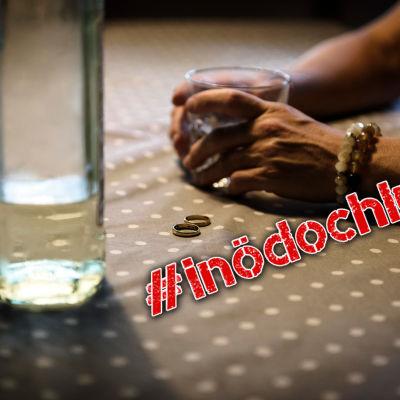 Flaska, två vigselringar och kvinnohänder med ett glas i handen.
