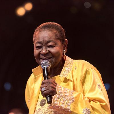 Sångerskan Calypso Rose sjunger i en mikrofon
