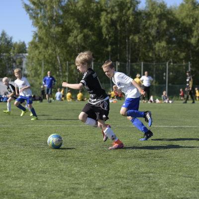 En spelare från SJK springer i kapp med en spelare från Kuffen under ett anfall under en fotbollsmatch.
