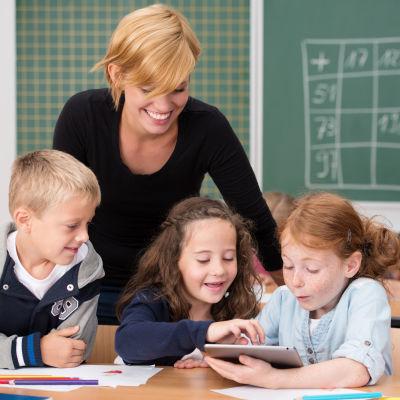 Tre skolelever med en läsplatta sitter vid ett bord. Den kvinnliga läraren lutar sig över eleverna.