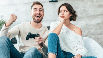 man spelar tv-spel och jublar, kvinna ser tveksamt på honom