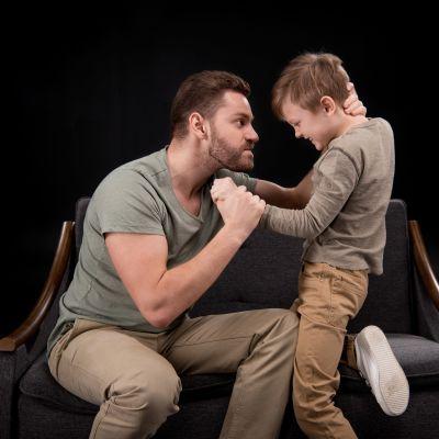 en pappa är arg och tar hårt i sin sons nacke och hand