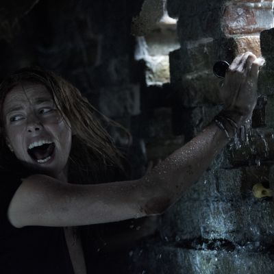 Närbild av Haley som klänger sig fast vid en fönsterglugg och skriker.