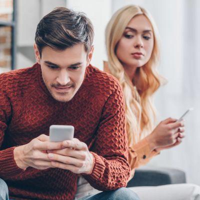Småleende man ser på sin mobil medan en kvinna misstänksamt ser över hans axel