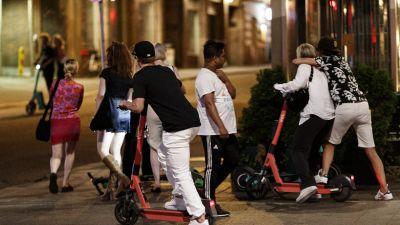 En person åker elsparkcykel på trottoar på natten. Två personer bakom honom åker på samma elsparkcykel.