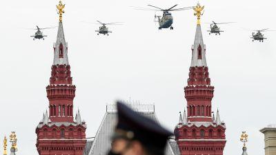 Militärhelikoptrar över Kreml under flyguppvisningen på segerdagen 9.5. En soldat i mask i förgrunden.