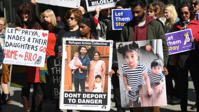 Demonstranter som håller upp plakat med bilder på familjen Murugappan.