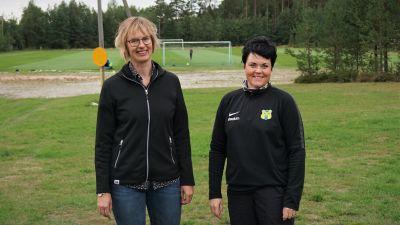 Två kvinnor står vid en sportplan.