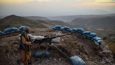 En turbanförsedd milisman står bakom en maskingevär i bergig terräng