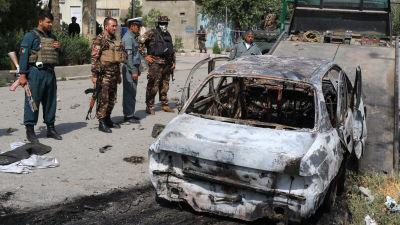 Till vänster poliser och till höger ett sönderbränt bilkadaver.