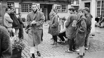 Paul Weller ulkona kävelee kohti kameraa pitkässä takissa, nuoriso katselee. Kuva dokumenttielokuvasta.