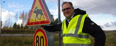 En man i reflexväst står vid en trafikskylt.