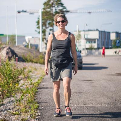 En gladkvinna promenerar för en asfalterad gata. I bakgrunden synds träd.